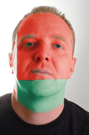 whose: High key portrait of a serious man whose face is painted in national colors of belarus