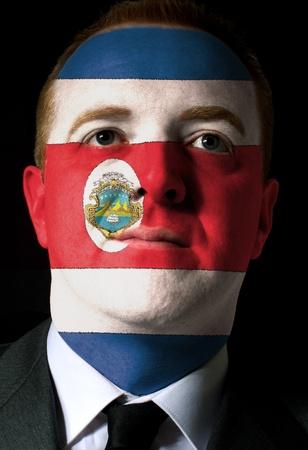 bandera de costa rica: Alto clave retrato de un hombre de negocios serio o un político cuyo rostro está pintado con los colores nacionales de la bandera de Costa Rica