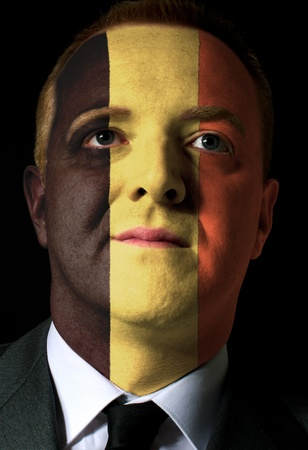 High key portrait of a serious businessman or politician whose face is painted in national colors of belgium flag photo