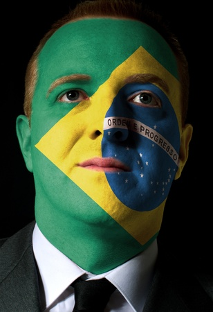 High key portrait of a serious businessman or politician whose face is painted in national colors of brazil flag