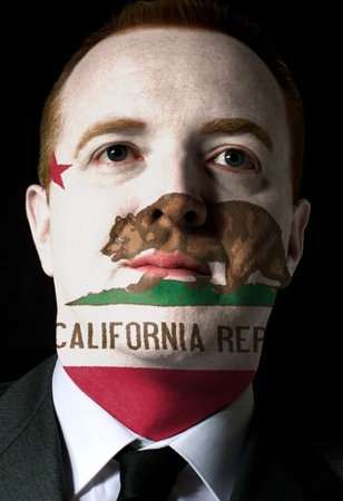 nationalism: High key portrait of a serious businessman or politician whose face is painted in american state of west california flag Stock Photo