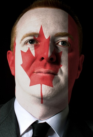 High key portrait of a serious businessman or politician whose face is painted in national colors of canada flag photo