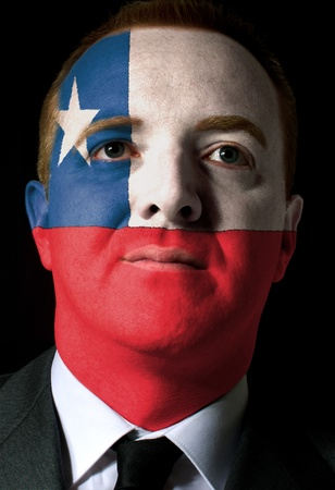 whose: High key portrait of a serious businessman or politician whose face is painted in national colors of chile flag
