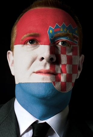 High key portrait of a serious businessman or politician whose face is painted in national colors of croatia flag photo
