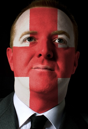 High key portrait of a serious businessman or politician whose face is painted in national colors of england flag photo