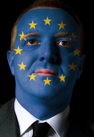 High key portrait of a serious businessman or politician whose face is painted in national colors of europe flag photo