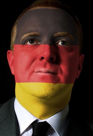 High key portrait of a serious businessman or politician whose face is painted in national colors of germany flag photo