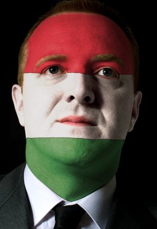 whose: High key portrait of a serious businessman or politician whose face is painted in national colors of hungary flag Stock Photo