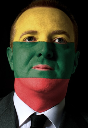 whose: High key portrait of a serious businessman or politician whose face is painted in national colors of lithuania flag