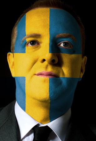 High key portrait of a serious businessman or politician whose face is painted in national colors of sweden flag photo
