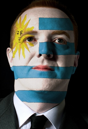 High key portrait of a serious businessman or politician whose face is painted in national colors of uruguay flag photo