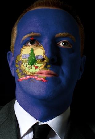 Alto clave retrato de un hombre de negocios serio o un político cuyo rostro está pintado en el estado norteamericano de Vermont bandera