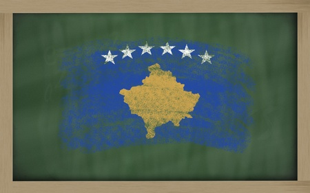 Chalky kosovo flag painted with color chalk on old blackboard photo