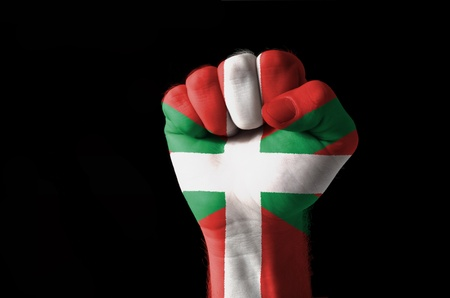 Low key picture of a fist painted in colors of basque flag