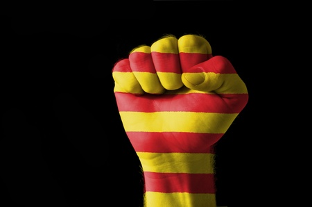 nationalism: Low key picture of a fist painted in colors of catalonia flag