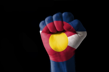 Low key picture of a fist painted in colors of american state flag of colorado