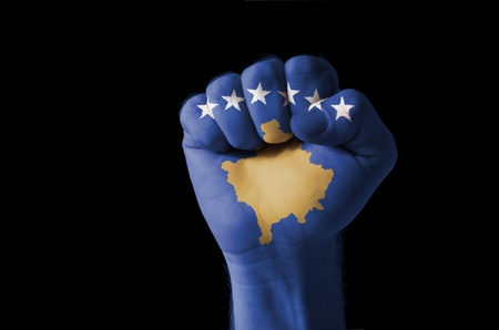 Low key picture of a fist painted in colors of kosovo flag photo