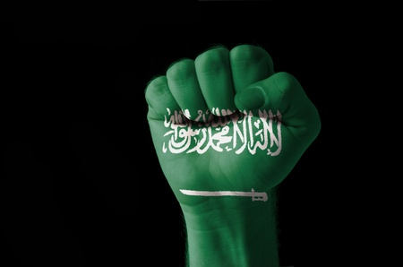 arabia: Low key picture of a fist painted in colors of saudi arabia flag