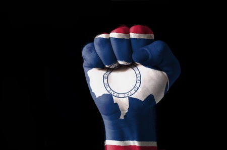 Low key picture of a fist painted in colors of american state flag of wyoming Standard-Bild