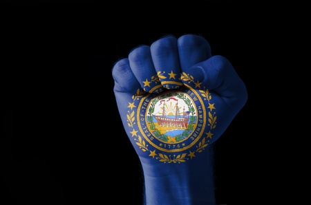 Low key picture of a fist painted in colors of american state flag of new hampshire photo