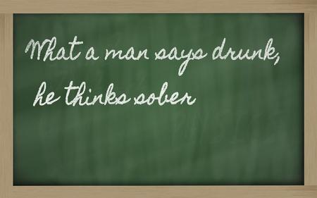 he: handwriting blackboard writings - What a man says drunk, he thinks sober Stock Photo
