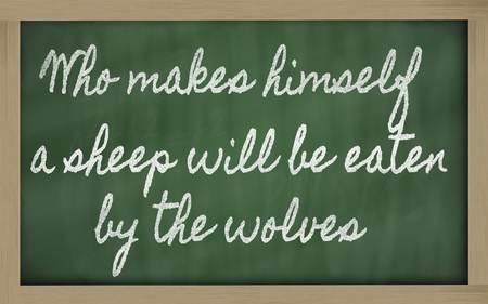 handwriting blackboard writings - Who makes himself a sheep will be eaten by the wolves Фото со стока