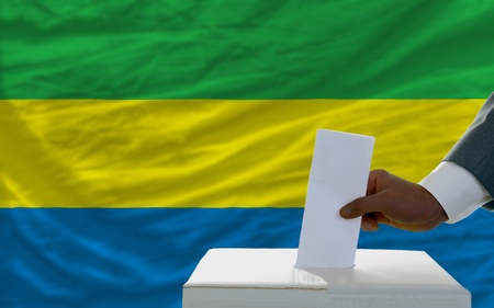 ballot box: man putting ballot in a box during elections  in front of national flag of gabon