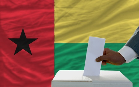 man putting ballot in a box during elections  in front of national flag of guinea photo