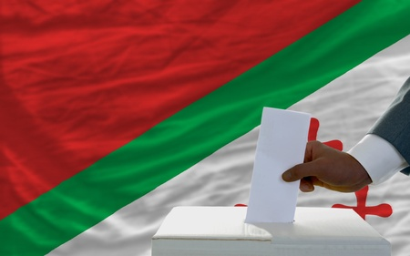 man putting ballot in a box during elections  in front of national flag of katanga photo