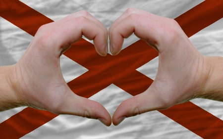Gesture made by hands showing symbol of heart and love over us state flag of alabama Stock Photo - 12478685