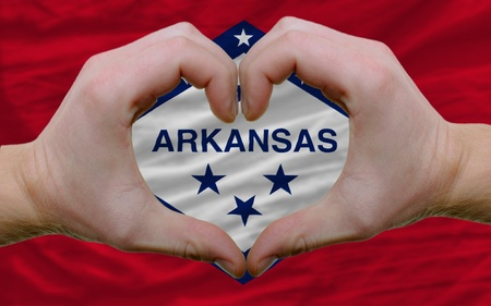 Gesture made by hands showing symbol of heart and love over us state flag of arkansas