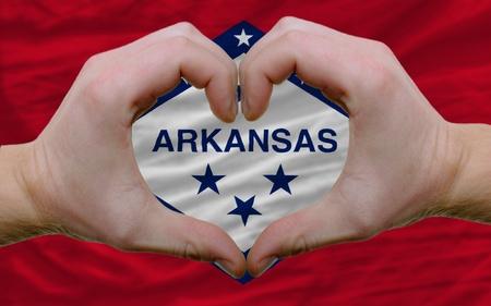 Gesto compiuto da mani che mostrano il simbolo del cuore e l'amore su di noi bandiera dello stato dell'Arkansas Archivio Fotografico - 12478676