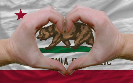 Gesture made by hands showing symbol of heart and love over us state flag of california photo