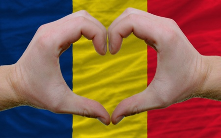 chadian: Gesture made by hands showing symbol of heart and love over flag of chad Stock Photo