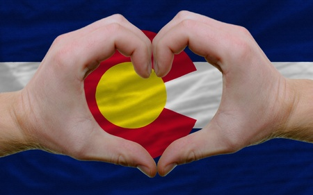 Gesture made by hands showing symbol of heart and love over us state flag of colorado