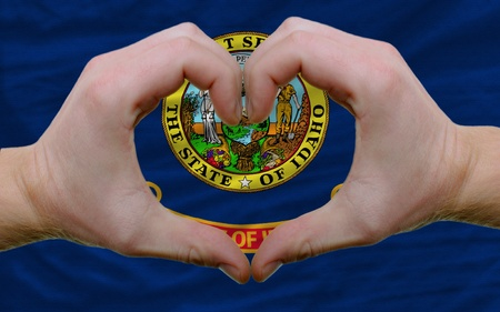 Gesture made by hands showing symbol of heart and love over us state flag of idaho photo