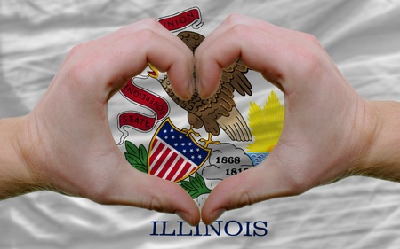 Gesture made by hands showing symbol of heart and love over us state flag of illinois photo