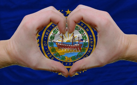 Gesture made by hands showing symbol of heart and love over us state flag of new hampshire photo