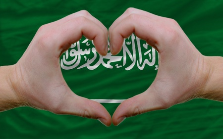 Gesture made by hands showing symbol of heart and love over flag of saudi arabia photo