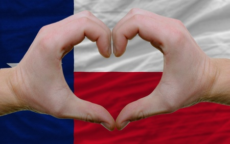 gesture: Gesture made by hands showing symbol of heart and love over us state flag of texas
