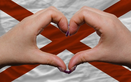 Gesture made by hands showing symbol of heart and love over us state flag of alabama photo