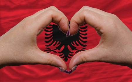 Gesture made by hands showing symbol of heart and love over national albania flag photo
