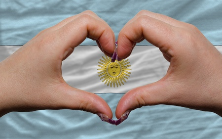 Gesture made by hands showing symbol of heart and love over national argentina flag photo
