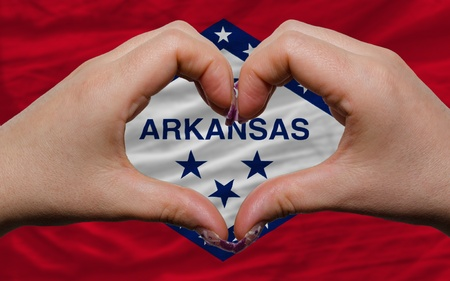 Gesture made by hands showing symbol of heart and love over us state flag of arkansas photo