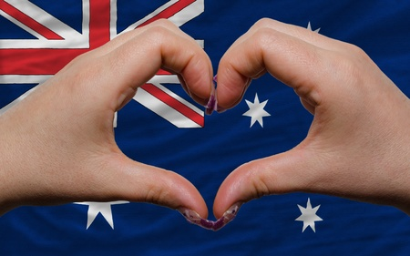 Gesture made by hands showing symbol of heart and love over national australia flag photo