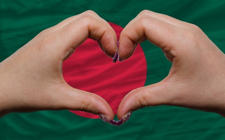 national colors: Gesture made by hands showing symbol of heart and love over national bangladesh flag