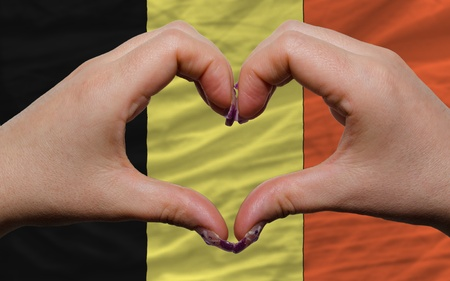 made in belgium: Gesture made by hands showing symbol of heart and love over national belgium flag