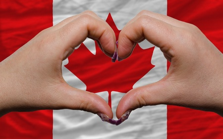 canadian state flag: Gesture made by hands showing symbol of heart and love over national canada flag