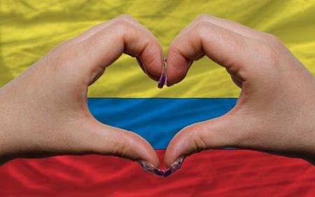 Gesture made by hands showing symbol of heart and love over national colombia flag photo