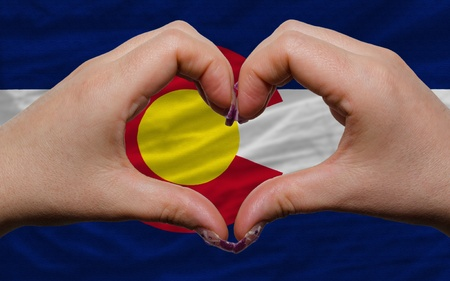Gesture made by hands showing symbol of heart and love over us state flag of colorado photo